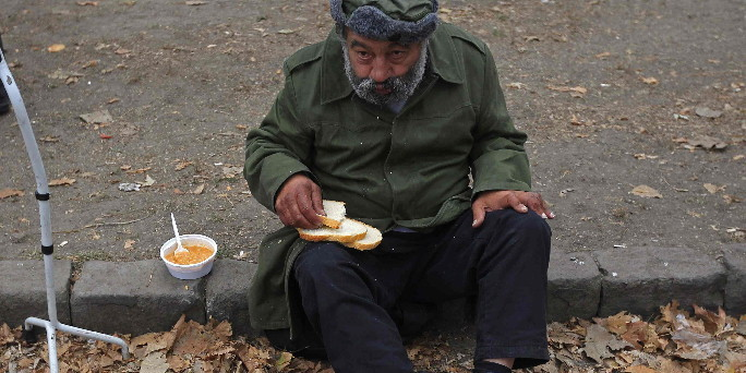 A man eats a free lunch received from Krishna followers in Budapest